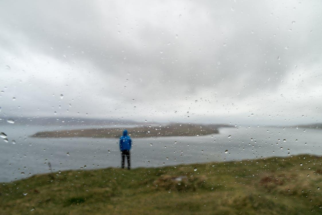 Man Standing on Grass Near Water