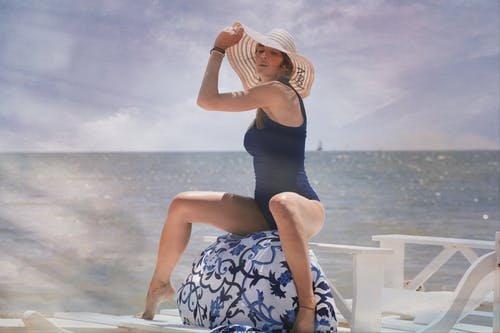 Woman In Blue Swimwear Sitting On White Wooden Bench