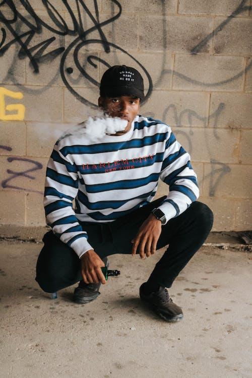 Man In Striped Sweater Vaping