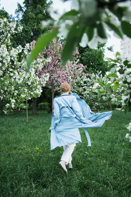 Stylish young woman in garden with blooming trees