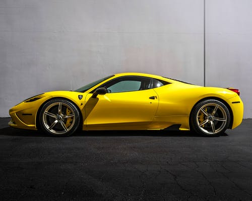 Yellow Ferrari 458 Italia Parked Beside White Wall