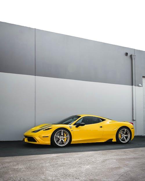 Yellow Ferrari 458 Italia Parked Beside Gray Wall