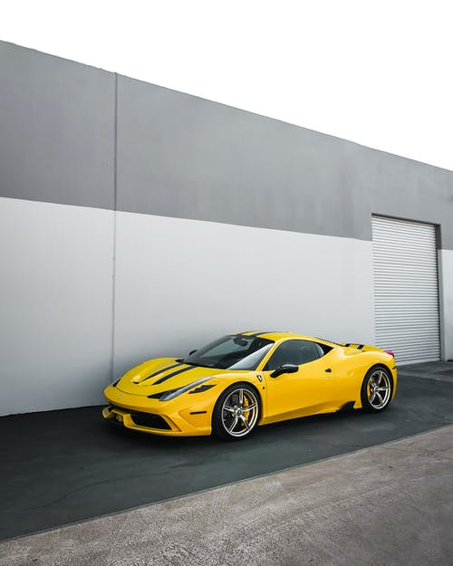 Yellow Ferrari 458 Italia Parked Beside Gray Wall