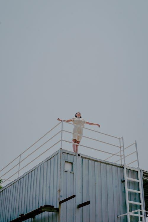 Man in White Shirt and Black Pants Jumping on White Metal Railings