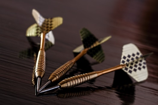 Brass Gold Darts on Brown Table