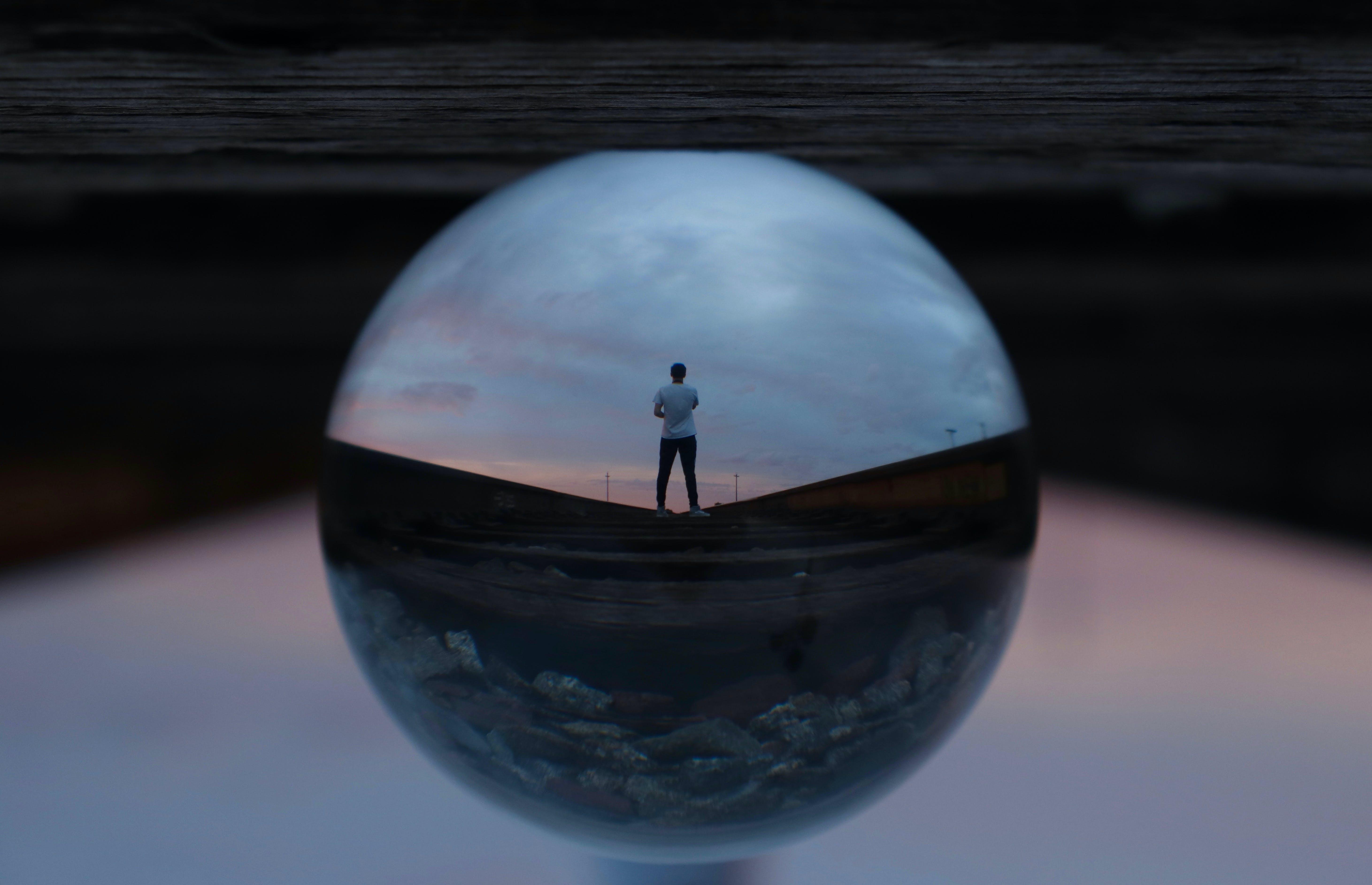 Round Glass Ball Reflecting Man Standing