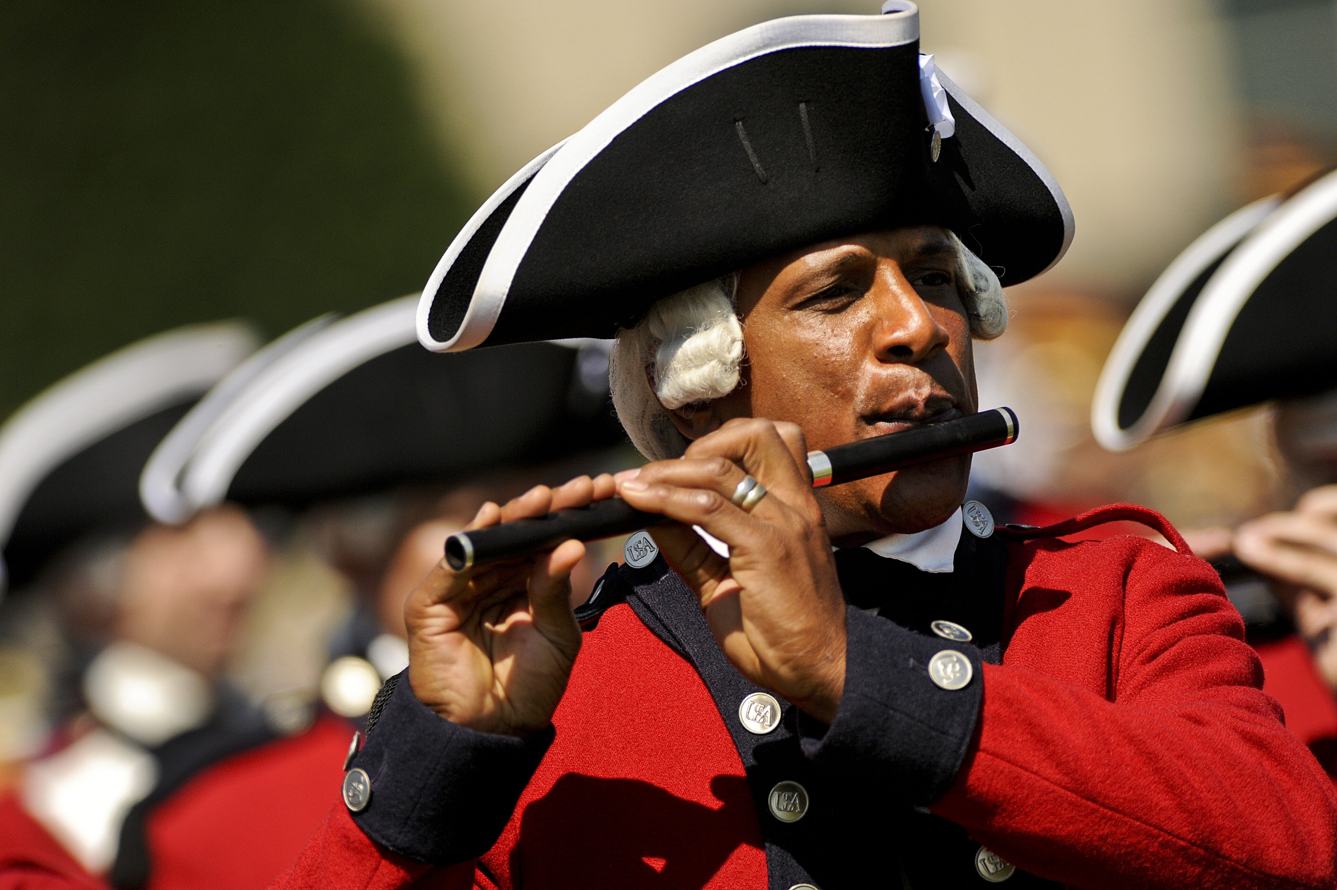 Man in Red and White Musical Suit Playing Flute during Daytime in Camera Focus Photography