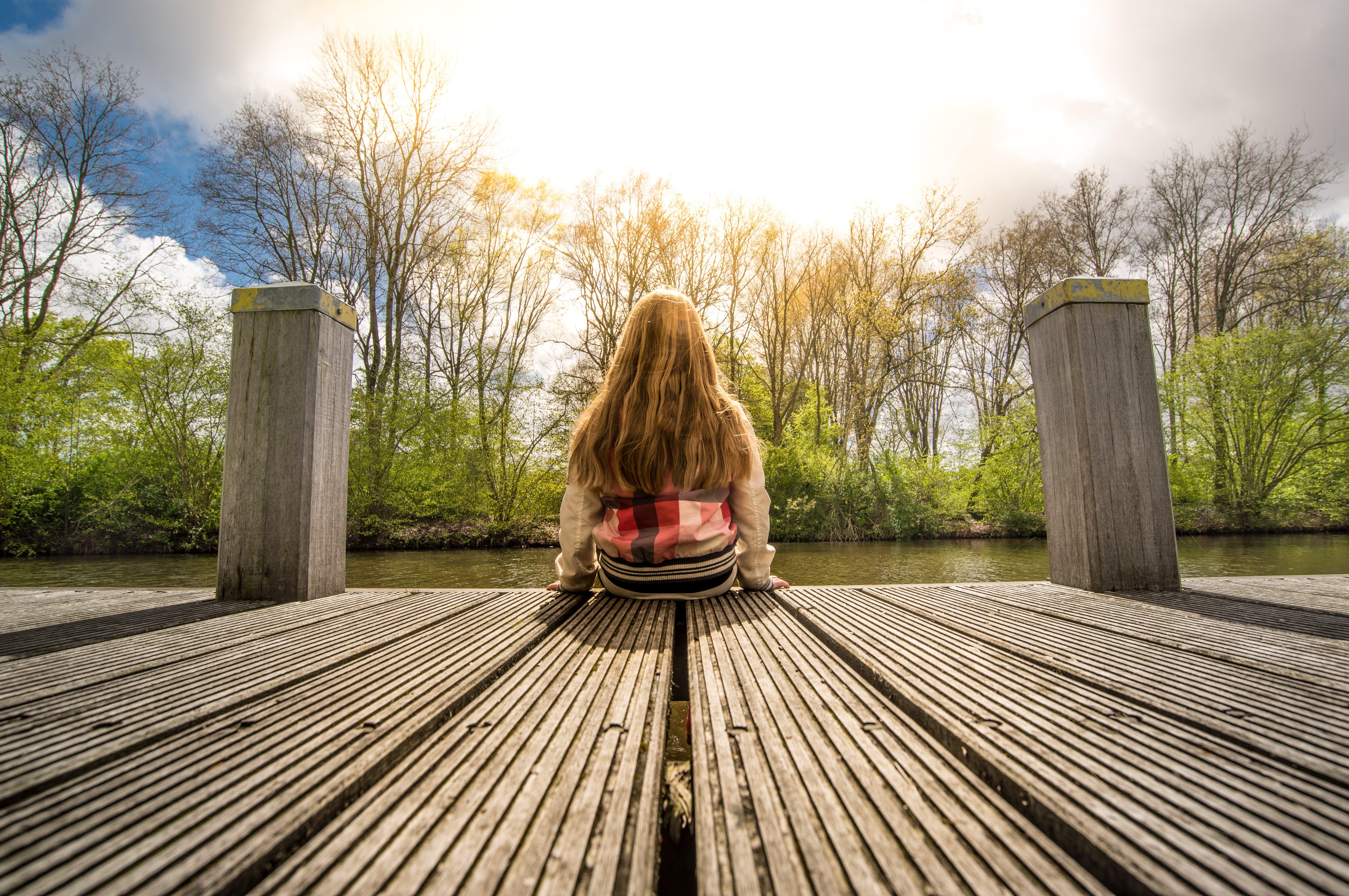 Woman Sitting Down on Bridge