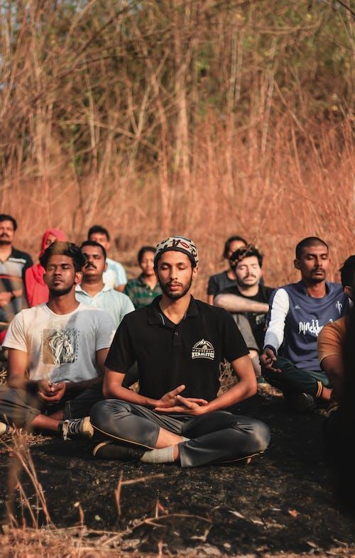 Grupo De Homens Sentados No Campo De Grama Marrom