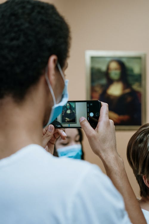 Man Taking Picture Of A Painting Of Mona Lisa Wearing Face Mask
