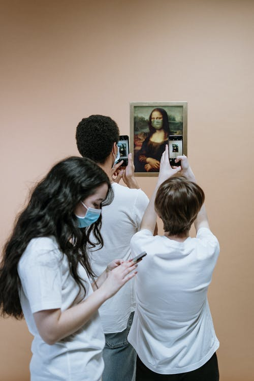 Three People Holding Their Phones And Taking Picture Of A Mona Lisa Painting