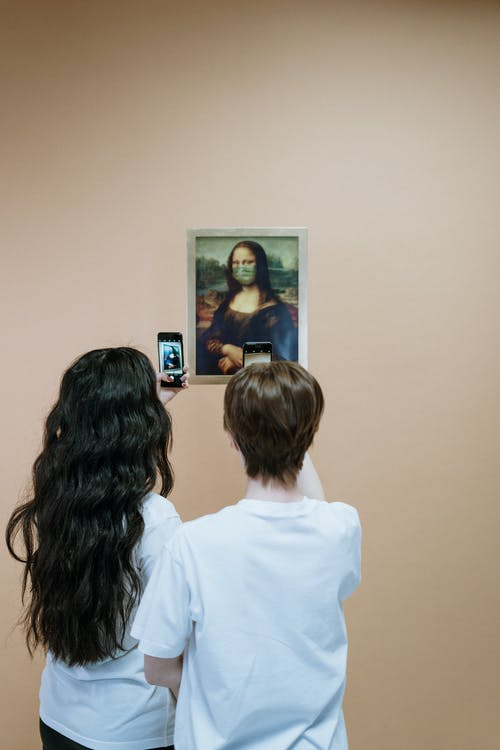 Two Women in White Shirt Taking Picture Of A Painting Of Mona LIsa With Face Mask
