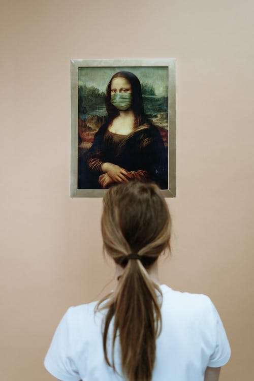Woman Looking At A Painting Of Mona Lisa Wearing Face Mask