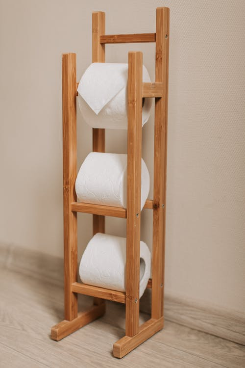 White Toilet Paper Rolls on Brown Wooden Rack