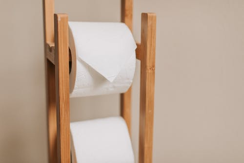 White Toilet Paper Roll on Brown Wooden Rack