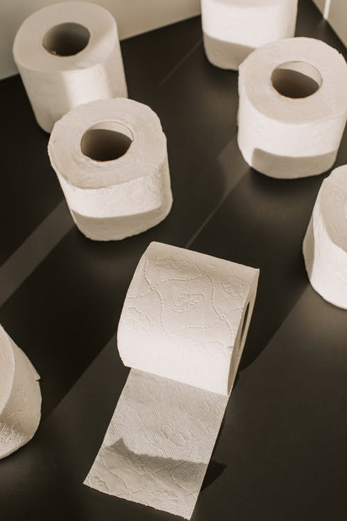 White Toilet Paper Rolls on Black Table