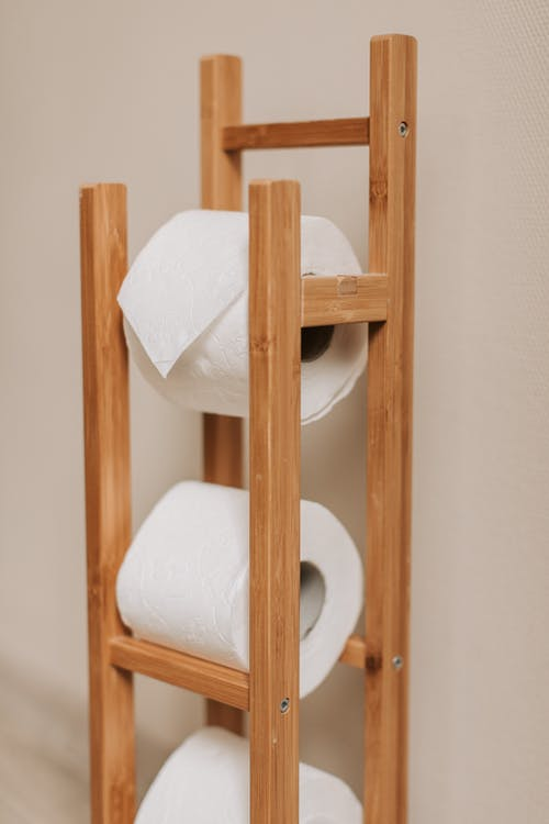 Toilet Paper Rolls on Brown Wooden Rack