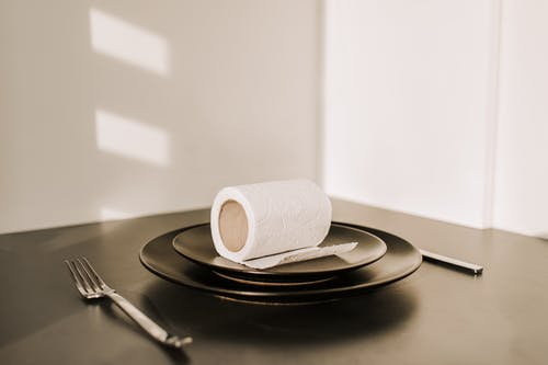 White Toilet Paper Roll on Black Plate