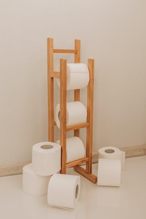 White Toilet Paper Rolls on Wooden Rack