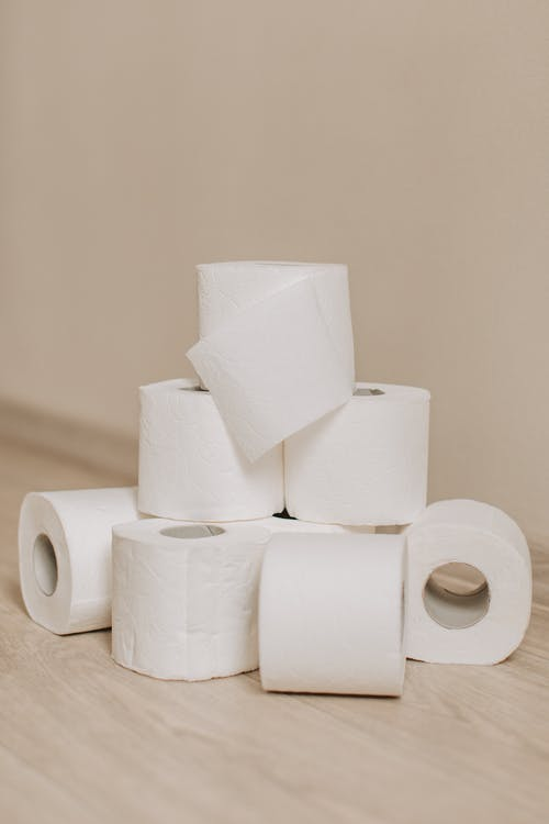 Tower of white toilet paper rolls placed on light wooden floor near wall as everyday need for hygiene and sanitary purposes