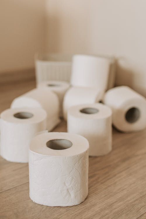 Set of white toilet paper tubes and plastic basket on bathroom floor