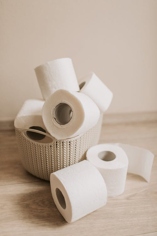 White toilet paper rolls placed inside plastic basket and near it on light wooden floor near wall as everyday need for hygiene and sanitary purposes