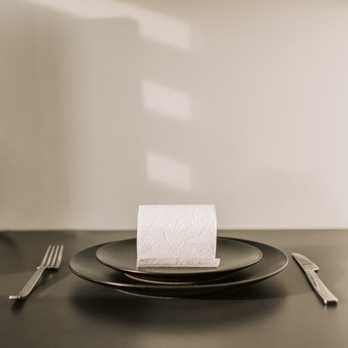 Toilet paper roll on dish with fork and knife