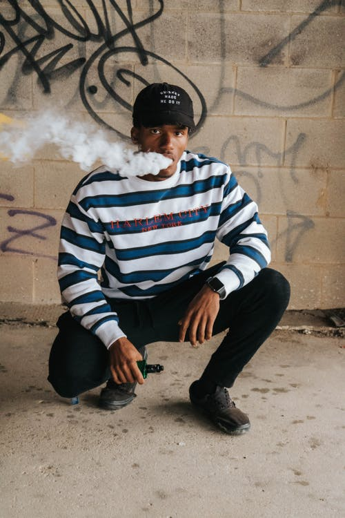 Man in Blue and White Striped Sweater Smoking Cigarette