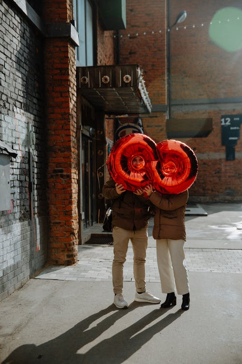 Happy couple with balloon standing on urban street in cold season
