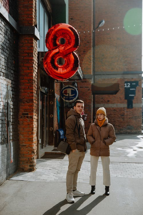 Confident couple with red foil balloon standing on urban street in cold season