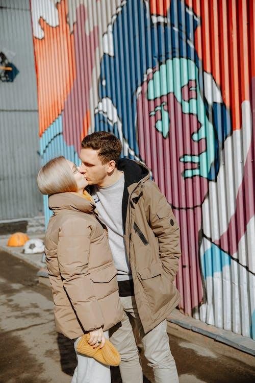 Man in Brown Coat Kissing Woman in Brown Coat