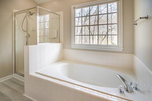 White Bathtub Near White Framed Window