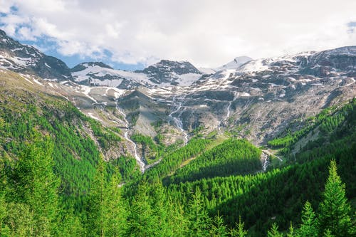 Green Trees and Snow Covered Mountains Under White Cloudy Sky