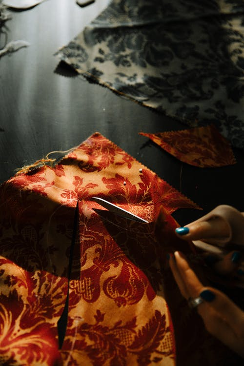 Unrecognizable young woman cutting fabric on table in tailor workshop