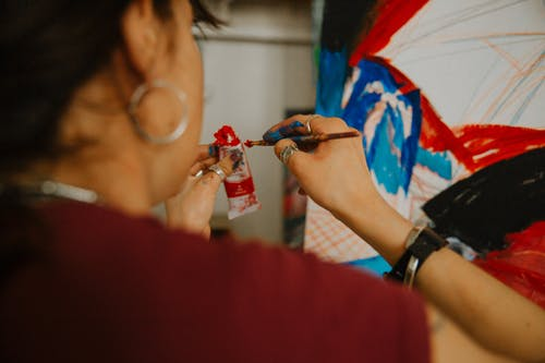Woman in Red Shirt Holding Blue and Red Paint