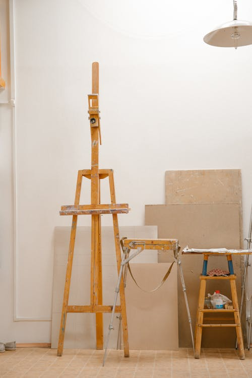 Easel and canvases inside artist workshop with minimal interior