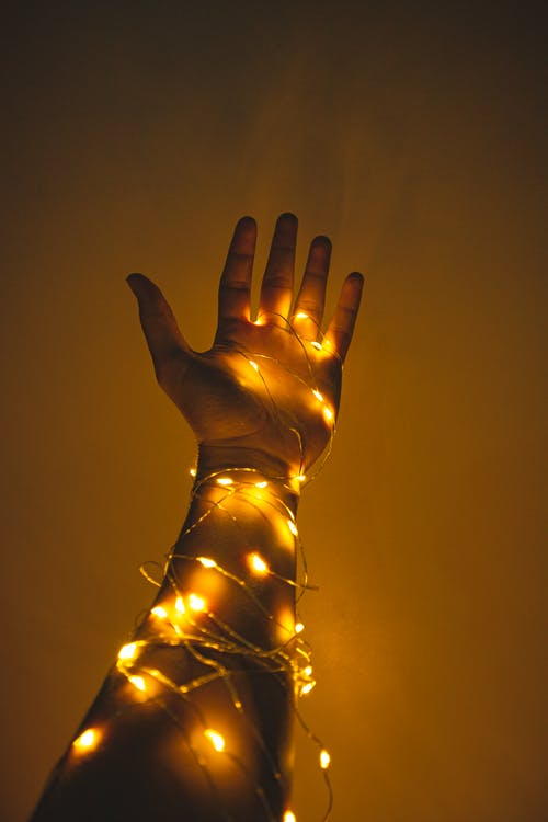 Person's Hand Wrapped in String Lights