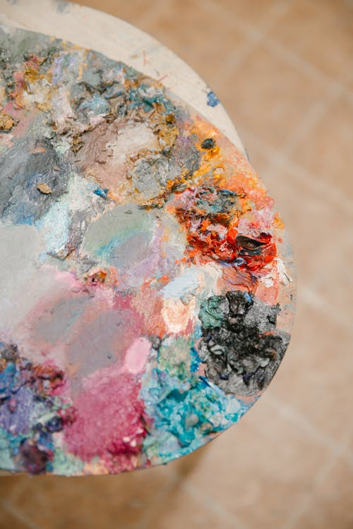 Top view of multicolored artist palette for creative painting work in art workshop on blurred background of brown tiles on floor