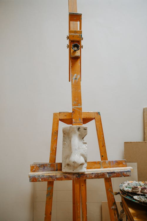 Wooden easel and sculpture of nose in art workshop