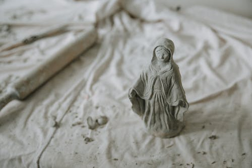 From above of clay statuette of woman placed on gray fabric with dusty rolling pin on aside in pottery workshop