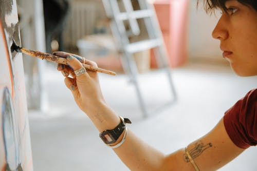 Side view of concentrated young woman in casual clothes drawing on canvas with paintbrush in hand while working in creative workshop