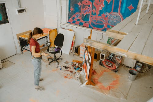 Full body of creative female artist standing against drawing on easel placed on floor in spacious workshop