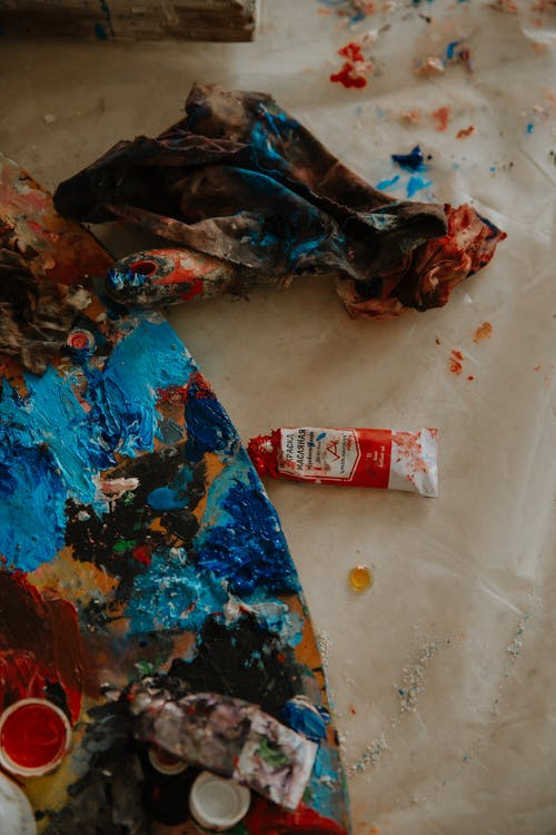 Paints squeezed onto round palette near dirty shred in painting workshop