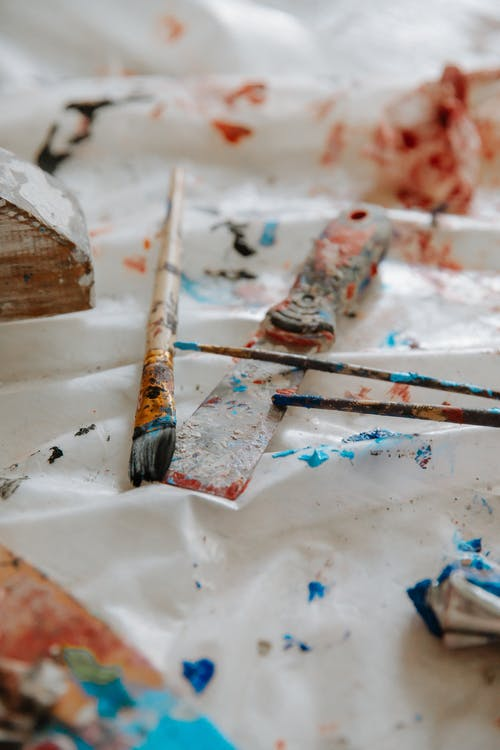 Dirty paintbrushes and painting spatula on oilcloth in light studio