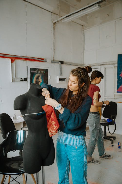 Stylish seamstress measuring size of pattern on mannequin while working in creative studio