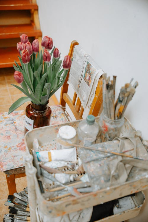 Paintbrushes and tools placed next to flowers in vase in art center