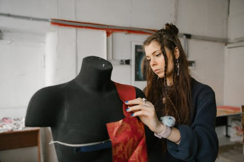 Focused female dressmaker preparing material on mannequin in workshop