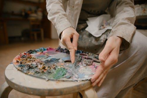 Crop artist mixing paints on palette