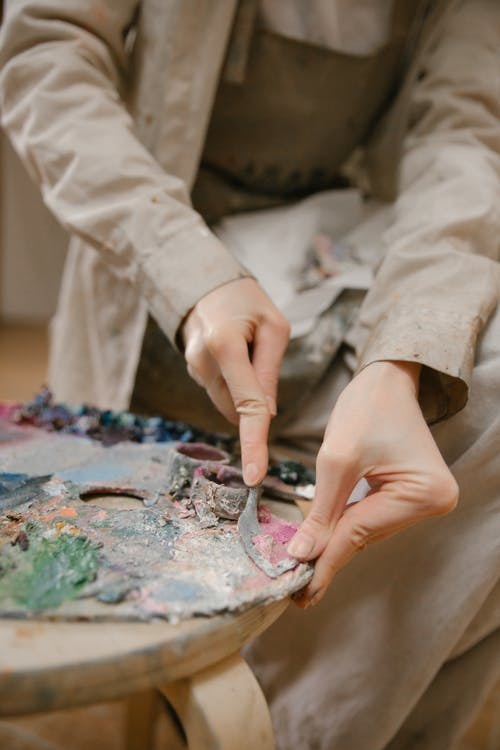 Crop artist scrubbing dry paint from palette