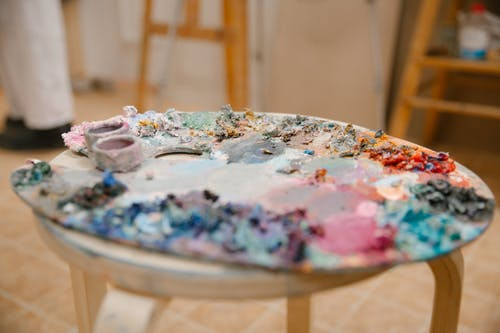 Palette of paints on chair in workshop